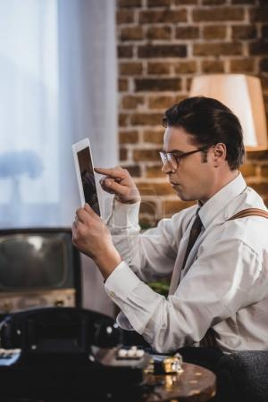 side view of old-fashioned man using digital tablet