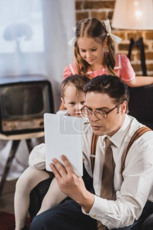 1950s style family using digital tablet at home