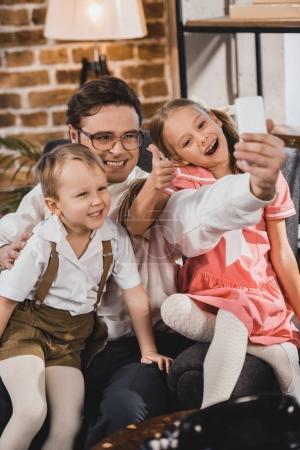 happy 1950s style family taking selfie with smartphone at home