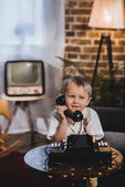 cute happy little boy talking by telephone, 1950s style
