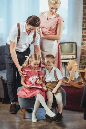 happy parents looking at cute little kids using digital tablet, 1950s style