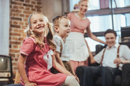 Photo for Adorable happy kids sitting on foreground while happy parents smiling behind, 1950s style - Royalty Free Image