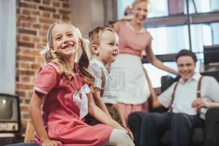 Photo pour Adorables enfants heureux assis sur le premier plan tandis que les parents heureux souriant derrière, style années 1950 - image libre de droit