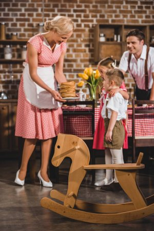 happy fifties styled family looking at smiling mother holding delicious pancakes