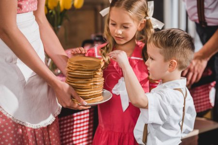 cropped shot of little brother and sister looking at delicious pancakes while mother holding plate, 50s style family