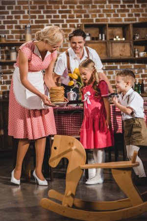 happy old-fashioned family looking at smiling mother holding delicious pancakes