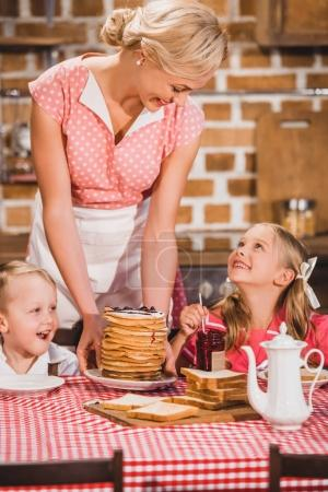 happy mother putting pancakes on table and looking at cute smiling kids having breakfast, 50s style family