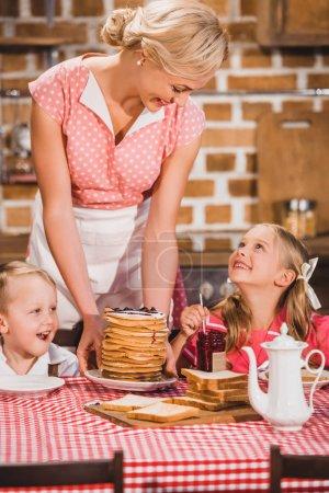 Foto de Panqueques poniendo madre feliz en mesa y mirar lindos sonrientes niños desayunando, 50s estilo familia - Imagen libre de derechos