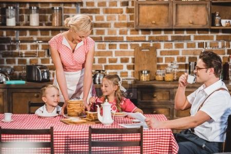 happy retro styled family having breakfast together