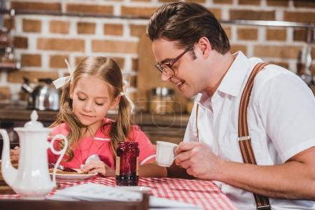 happy father and cute little daughter having breakfast together, 1950s style family