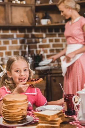 adorable little girl eating toast with jam and smiling at camera while mother washing dishes behind, 1950s style