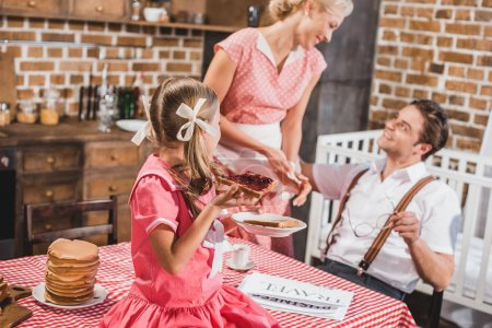 Photo for Happy parents with cute little child having breakfast together, 1950s style - Royalty Free Image