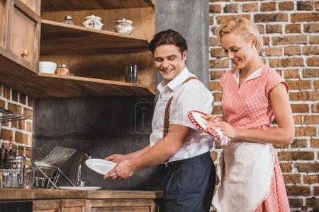 Photo pour Sourire des années 1950 couple laver et sécher la vaisselle ensemble dans la cuisine - image libre de droit