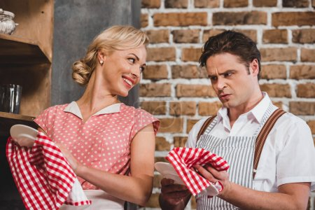 Photo for 50s style couple washing and drying dishes together - Royalty Free Image