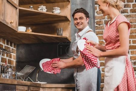 couple in aprons smiling each other while washing dishes together, 1950s style