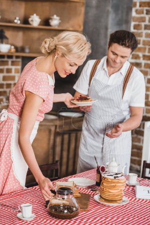 Photo for Happy couple in aprons serving table for breakfast, 1950s style - Royalty Free Image