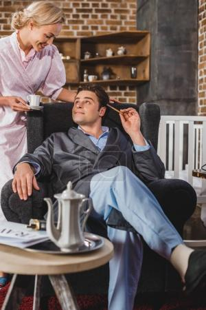 Photo for Smiling woman holding cup of coffee and looking at happy husband sitting in armchair, 50s style - Royalty Free Image