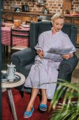 beautiful blonde woman in robe reading newspaper at home, 1950s style