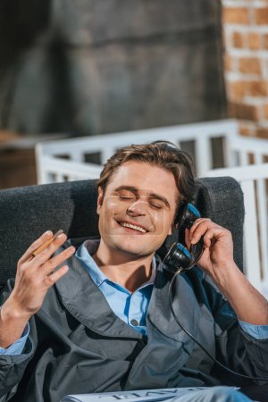 Photo for Happy man in robe smoking cigarette and talking by vintage telephone - Royalty Free Image