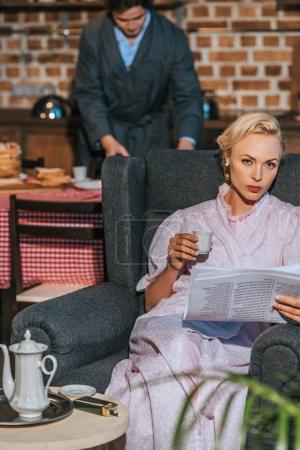 Photo for Woman in robe holding newspaper and cup of coffee while husband preparing breakfast behind, 1950s style - Royalty Free Image