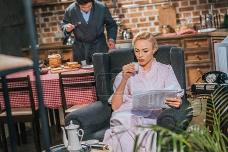 Photo for Woman in robe drinking coffee and reading newspaper while husband preparing breakfast behind, 1950s style - Royalty Free Image