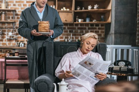 Photo for Cropped shot of man holding pancakes while woman in robe reading newspaper, 1950s style - Royalty Free Image