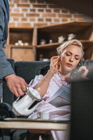 Foto de Recortada de tiro de hombre vertiendo café a esposa leyendo el periódico y hablar por teléfono vintage, años 50 estilo - Imagen libre de derechos