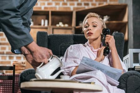 Photo for Cropped shot of husband pouring coffee to woman reading newspaper and talking by vintage telephone, fifties style - Royalty Free Image