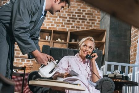 husband pouring coffee to happy wife talking by vintage telephone