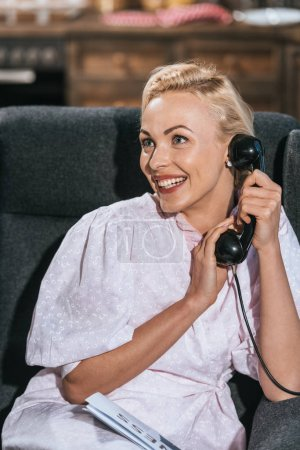 Photo for Happy blonde woman in robe talking by vintage telephone and looking away - Royalty Free Image