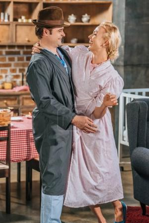 Photo for Happy 1950s style couple in robes dancing and smiling each other at home - Royalty Free Image