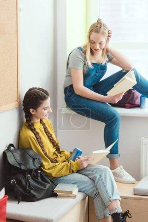 Photo pour Sourire des étudiantes de l'école secondaire avec livres parlant les uns aux autres - image libre de droit