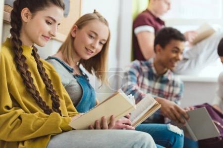 Photo pour Groupe d'adolescents multiculturels souriants lisant des livres pendant les vacances scolaires - image libre de droit