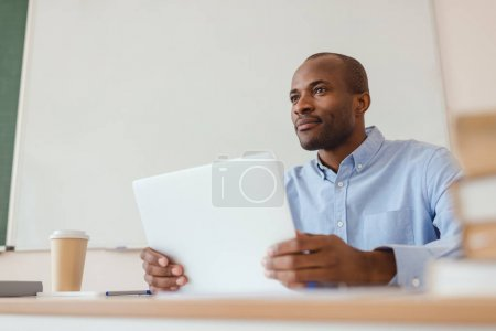 Low angle view of african american teacher sitting at desk with laptop and coffee cup