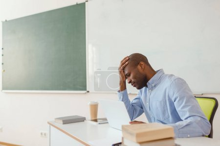 Tired african american teacher sitting at table with laptop and coffee cup in classroom
