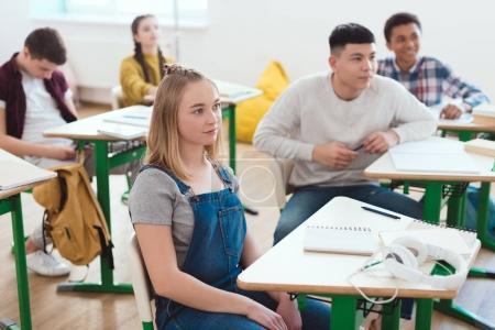 Foto de Grupo de estudiantes de secundaria adolescentes multicultural sentado en aula - Imagen libre de derechos