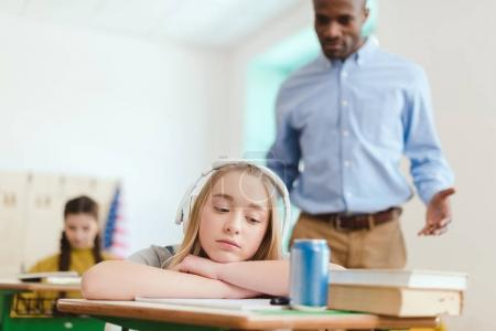 Dreamy high school teenage student listening music in headphones with classmate and teacher behind