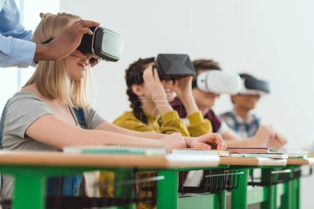 Cropped image of african american teacher adjusting virtual reality headset to teenage schoolgirl with classmates sitting behind