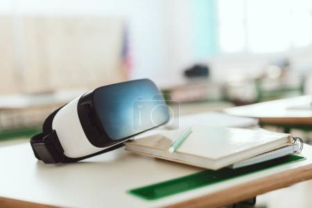 Closeup shot of virtual reality headset on table with textbook and pencil in classroom