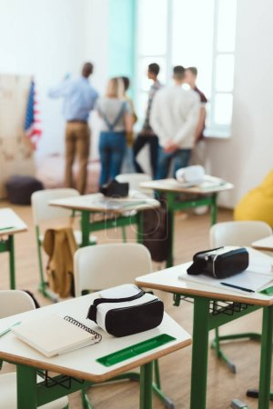 Virtual reality headsets on tables and teacher with schoolchildren standing behind