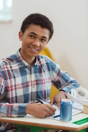 Portrait of african american high school student writing in textbook