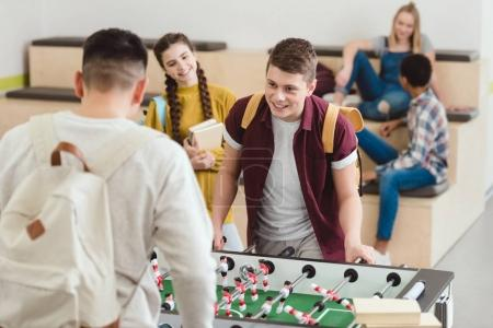 happy high school students playing table football at school corridor