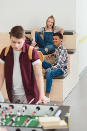 teenage students couple spending time together at school corridor and looking at kicker game