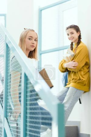 teenage schoolgirls standing on stairs and looking at camera
