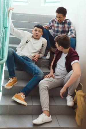 teenage schoolboys sitting on stairs at school