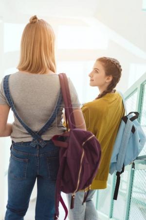 vue arrière des écolières avec sacs à dos, marche dans les escaliers au couloir de l'école
