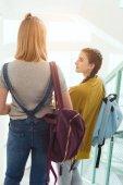 rear view of schoolgirls with backpacks walking down stairs at school corridor