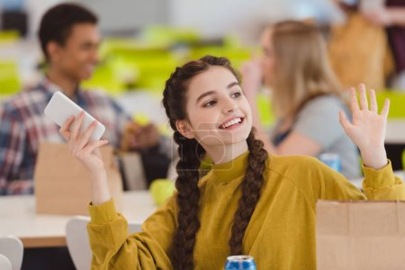 happy teen schoolgirl sitting at school cafeteria and greeting friend