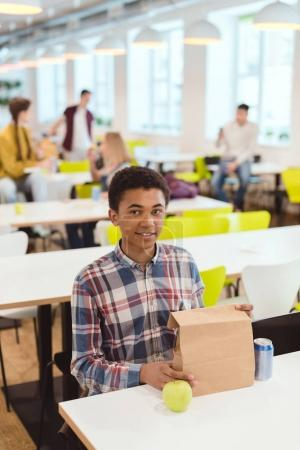african american schoolboy with lunch bag at school cafeteria