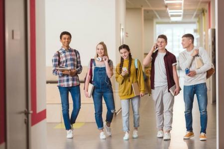 happy high school classmates walking by school corridor together